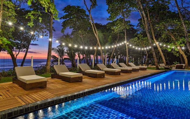 Deck chairs lined up by the pool at sunset