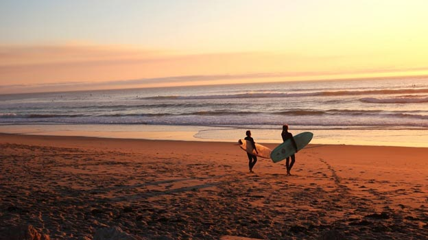 Two surfers on the beach at sunset