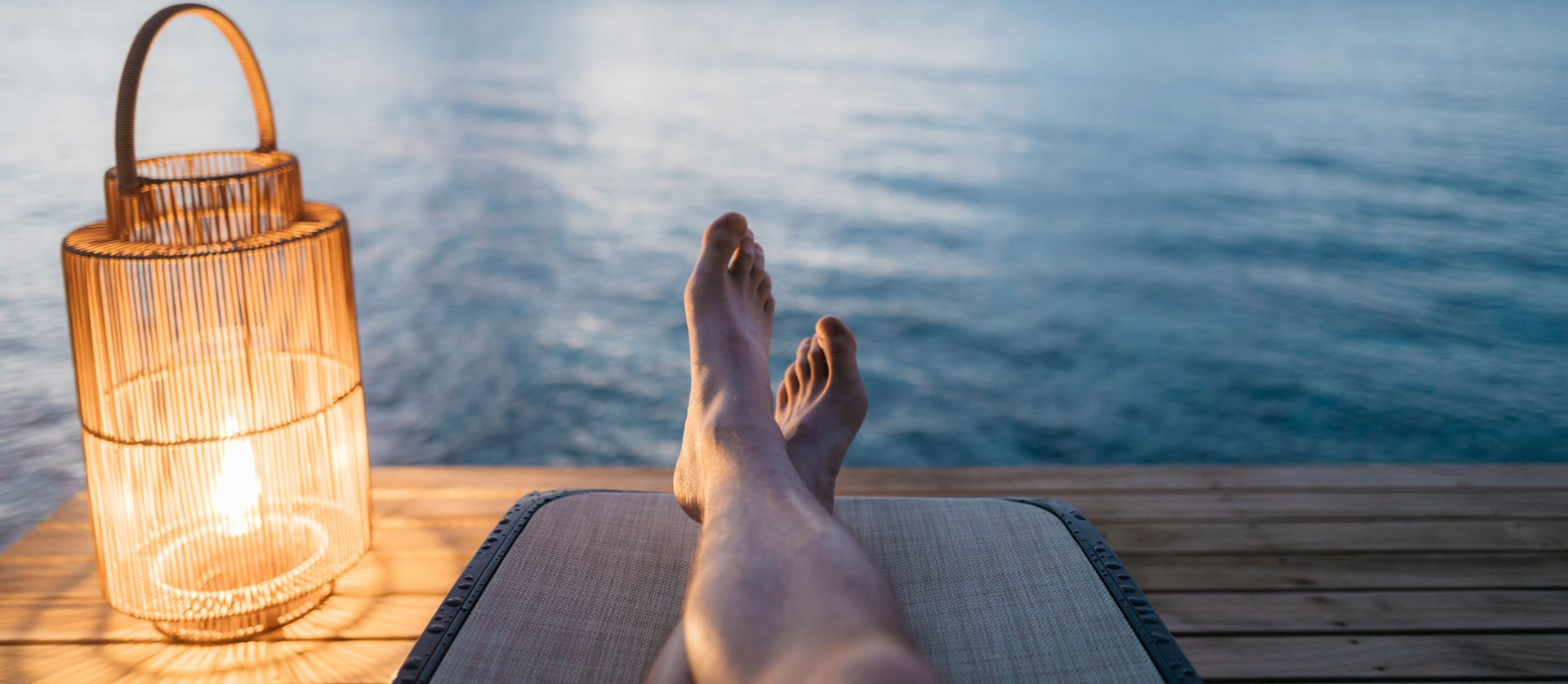 Feet on deck chair facing water