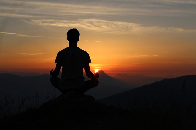 Man meditating on a mountain top at sunset