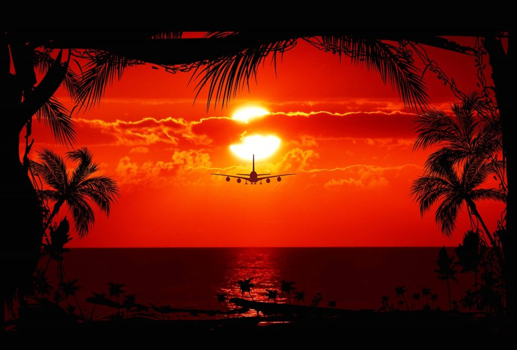 Plane flying low over the sea during the sunset.