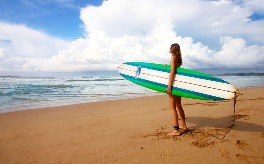 Woman on beach holding surfboard