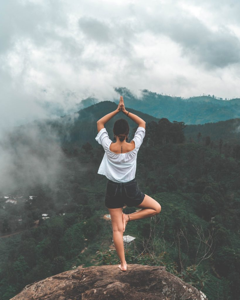 Woman doing yoga above jungle