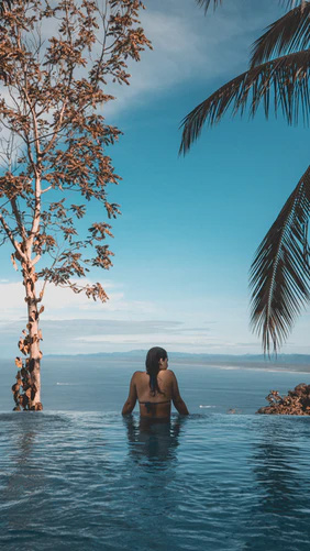 Back of woman in bikini in infinity pool