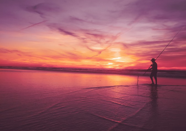 silhouette of man fishing in front of purple sunset