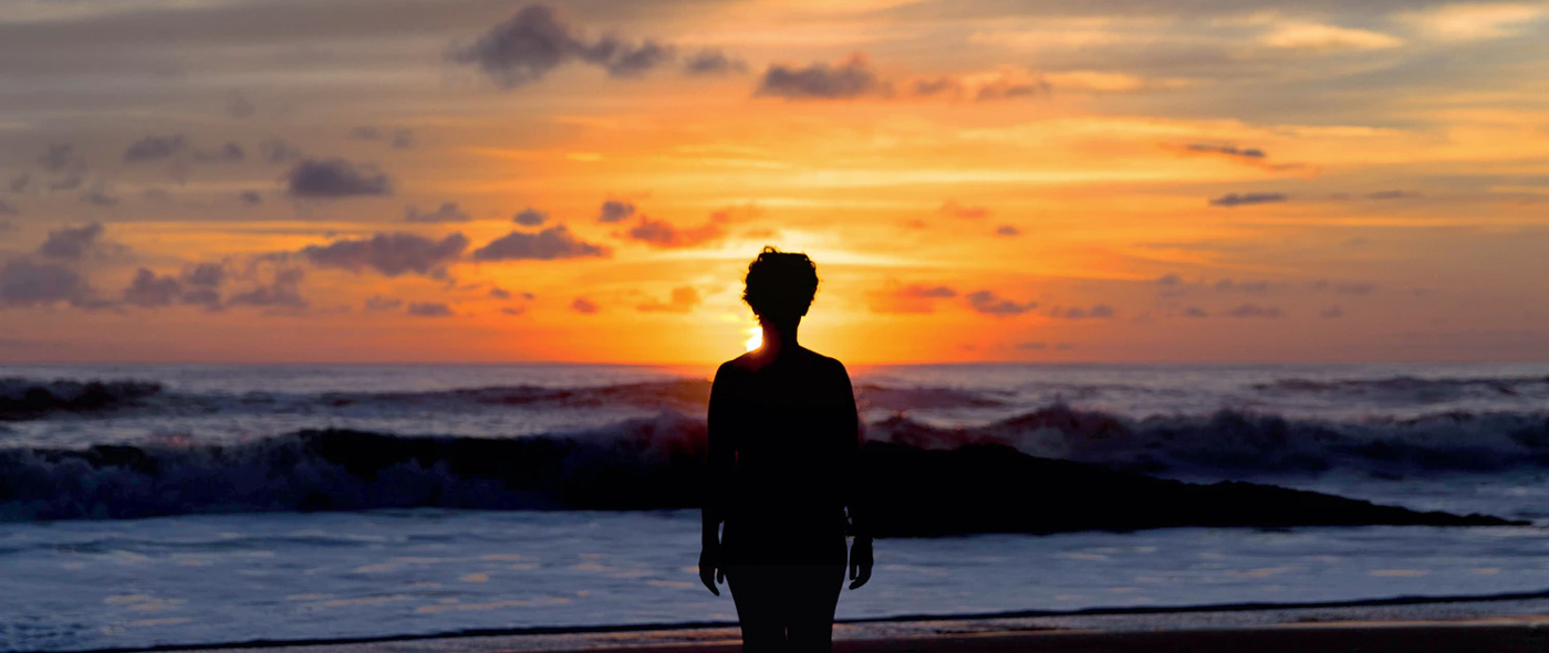 silhouetted woman in front of purple and orange sunset on beach