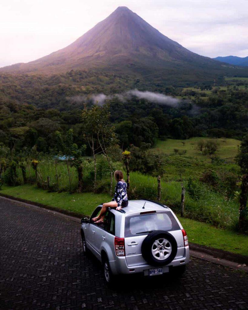 Woman sitting on car near tropical mountain
