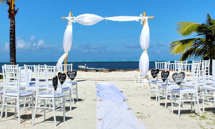 white archway and chairs set up for a wedding on the beach