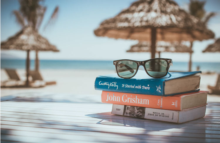 Books stacked on a picnic table overlooking the beach