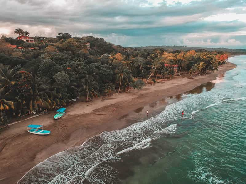 A Costa Rican beach with blue boats and lush forest