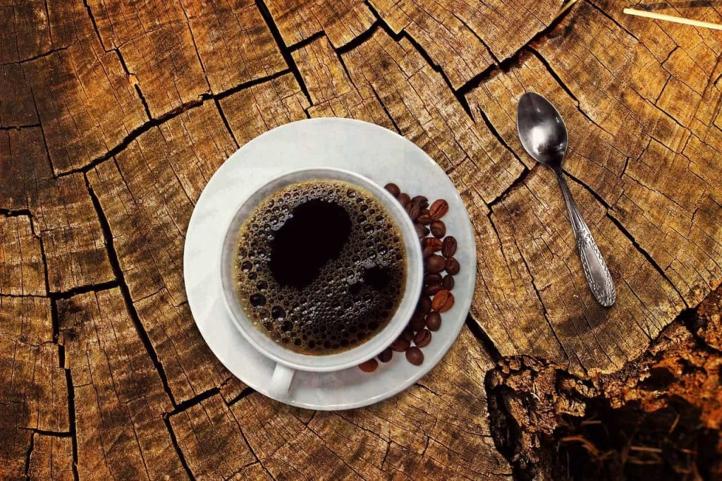 A cup of black coffee on a tree trunk table.
