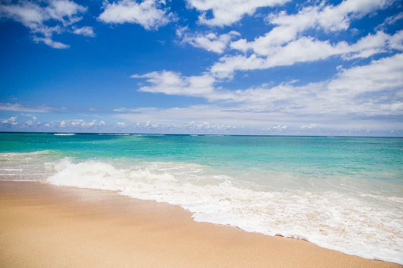 A stretch of white sandy beach and blue waters.