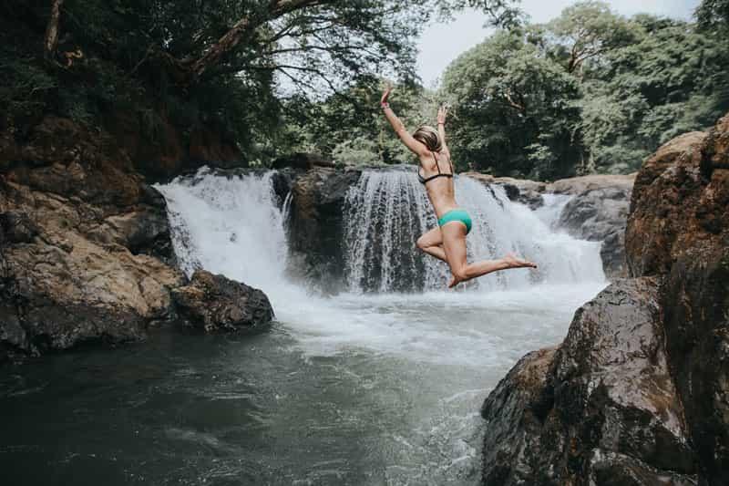 woman in bikini jumping off rocks into waterfall pool