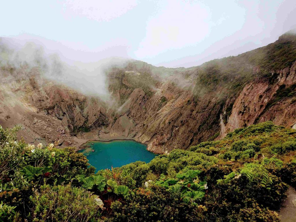 clouds and vegetation over a blue lagoon in volcan irazu national park, costa rica