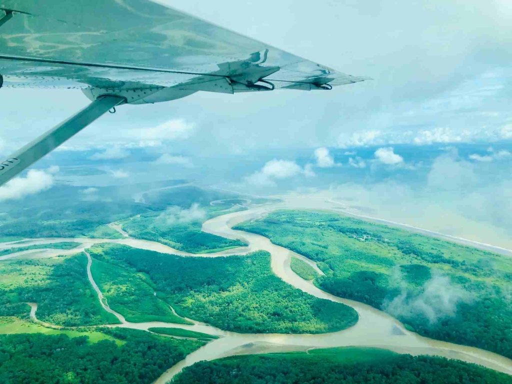 white plane wing over the rivers, forests, and ocean of drake bay costa rica