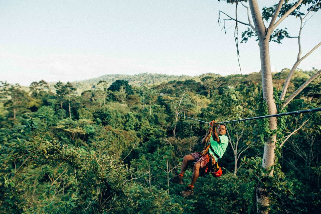 man ziplining over a rainforest canopy in costa rica
