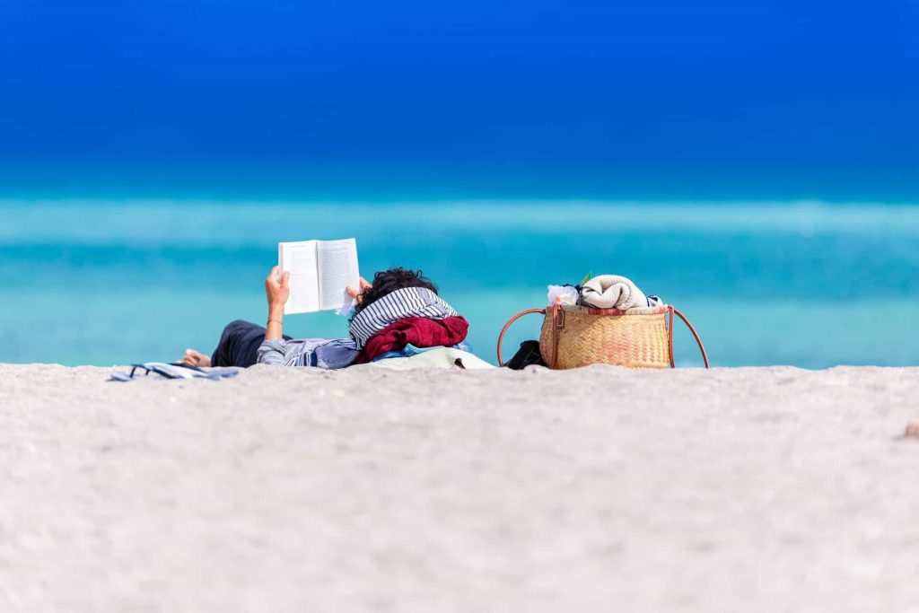 person lying on the shore reading a book next to bags and towels
