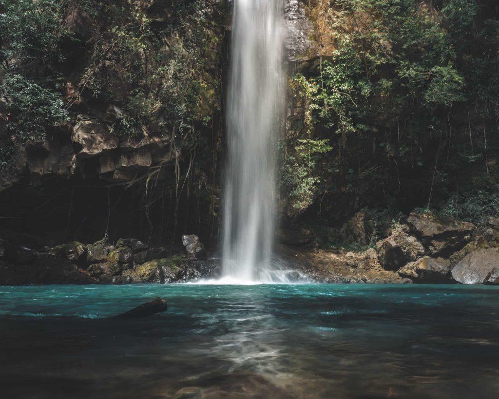 waterfall in a blue pool in Rincón de la Vieja, Costa Rica