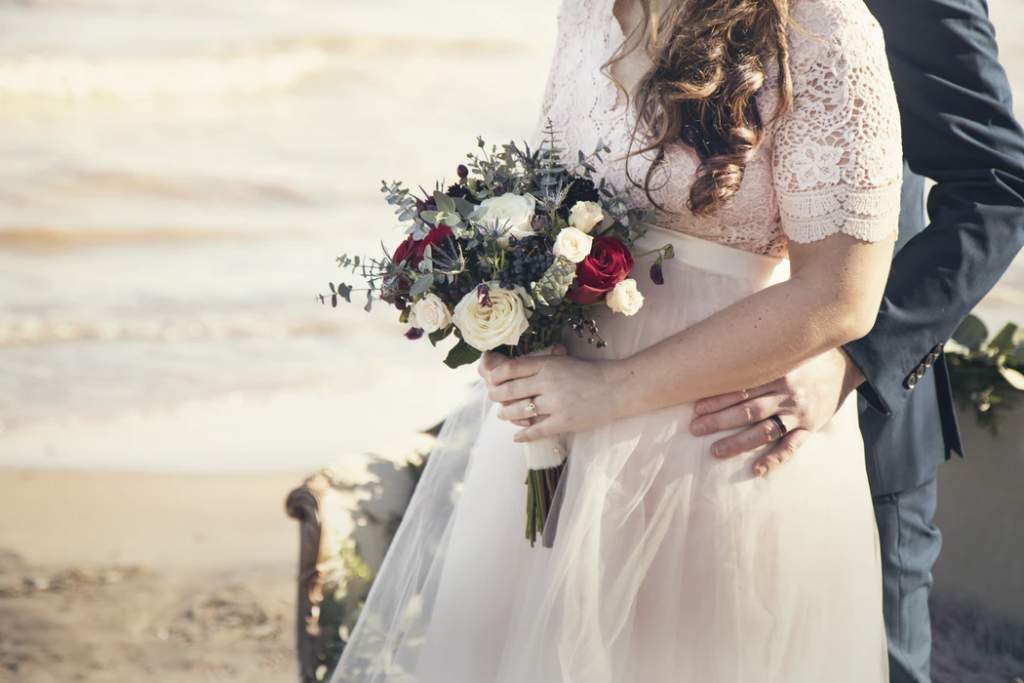 bride and groom holding bouquet of roses on a beach