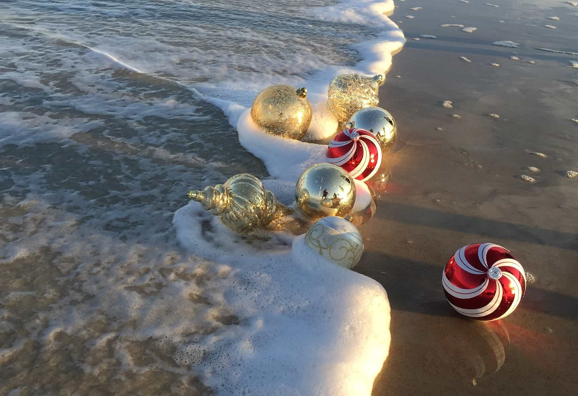 christmas ornaments washing up in the waves of a beach