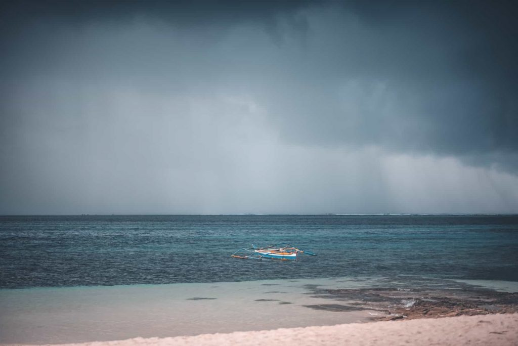 rain pouring from dark rainclouds over a beach