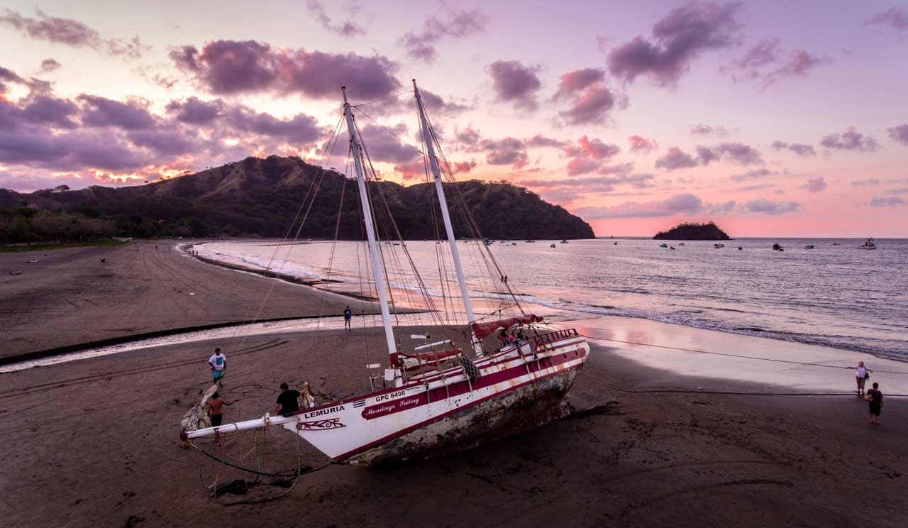 boat on a sandy beach in front of a pink and purple sky
