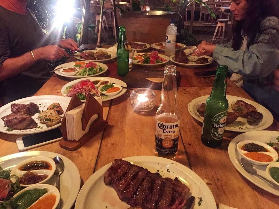 Beer and steak on a table with diners in the background.