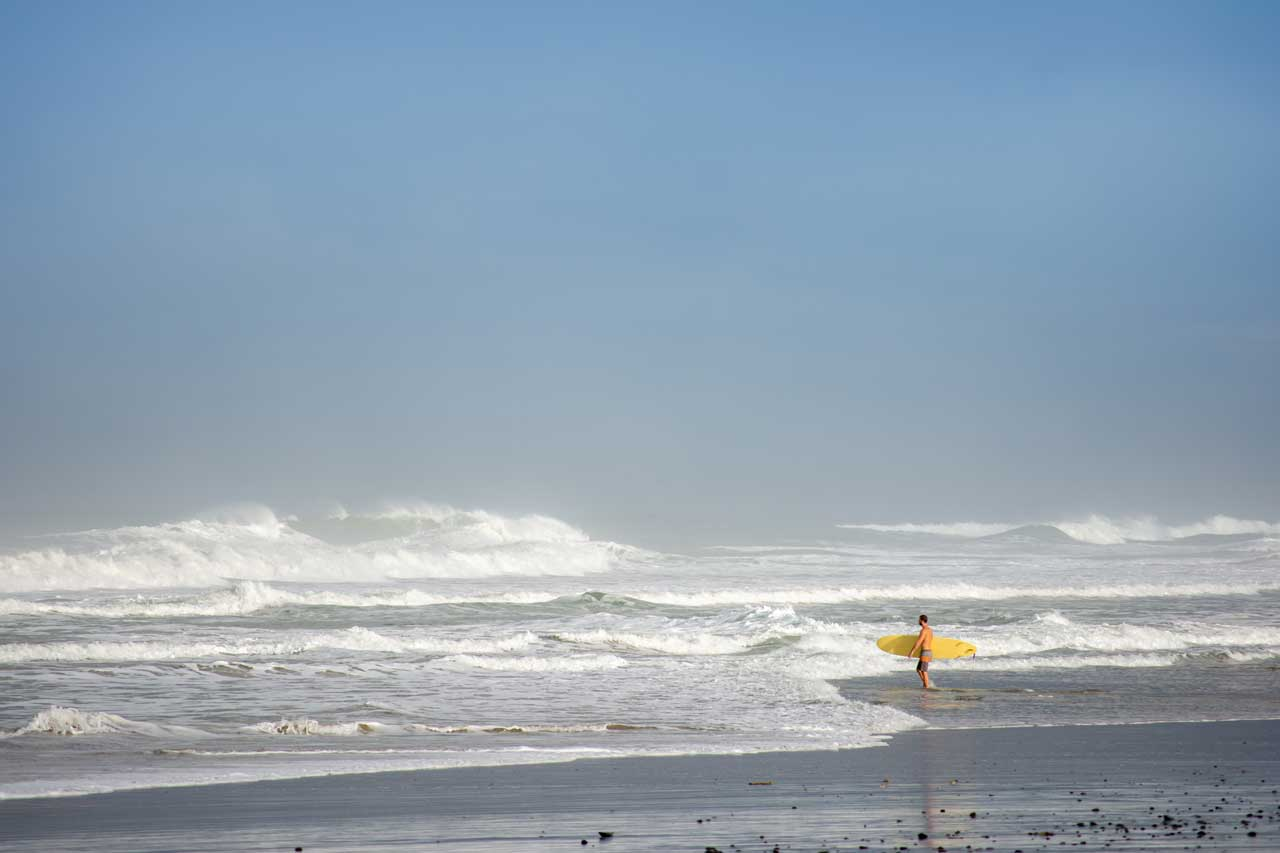 surfer with yellow surfboard walking into the waves