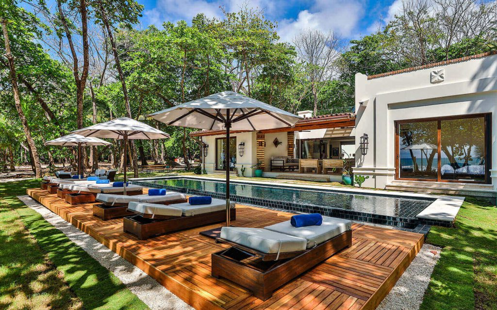 A swimming pool and poolside deck chairs at Casa Teresa, Costa Rica.