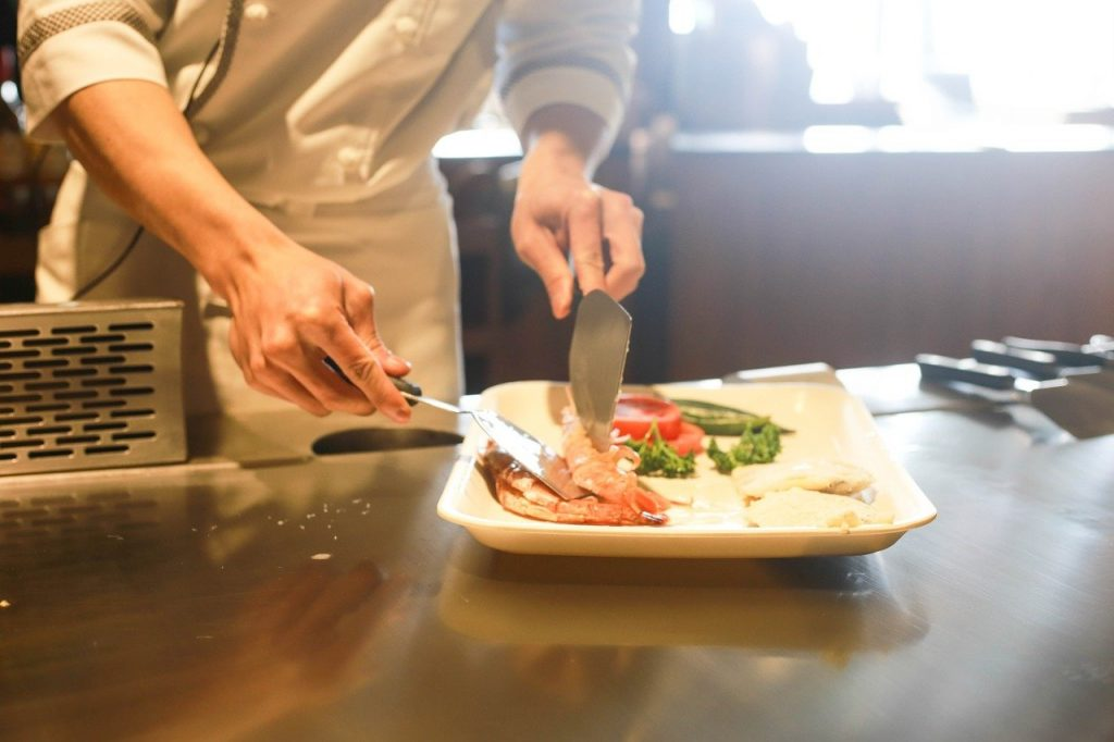 A private chef serving seafood onto a plate of salad