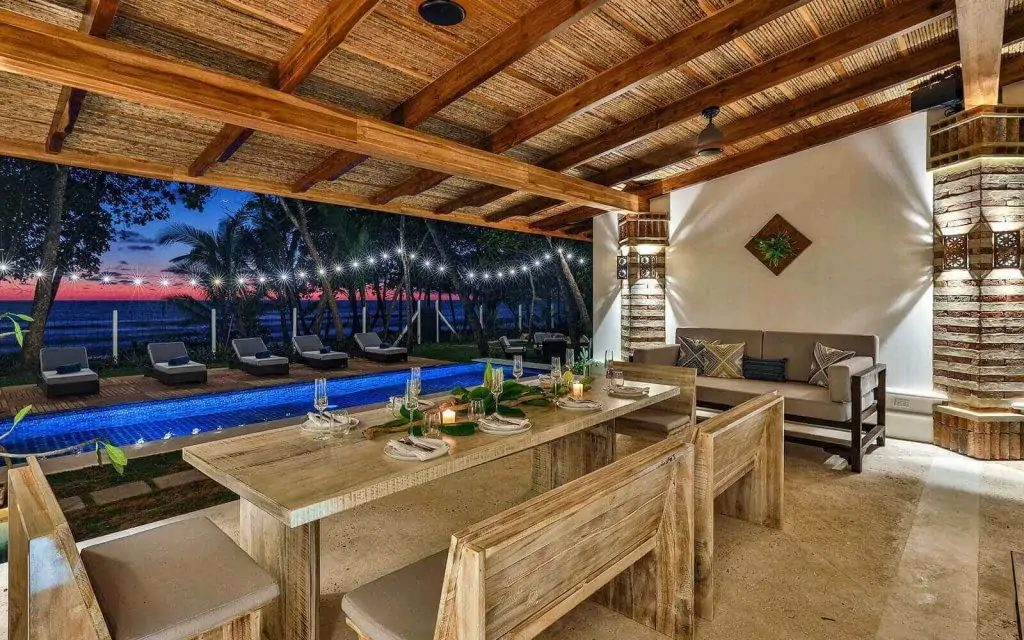 The alfresco dining area with a pool and ocean view at Casa Teresa at nighttime.