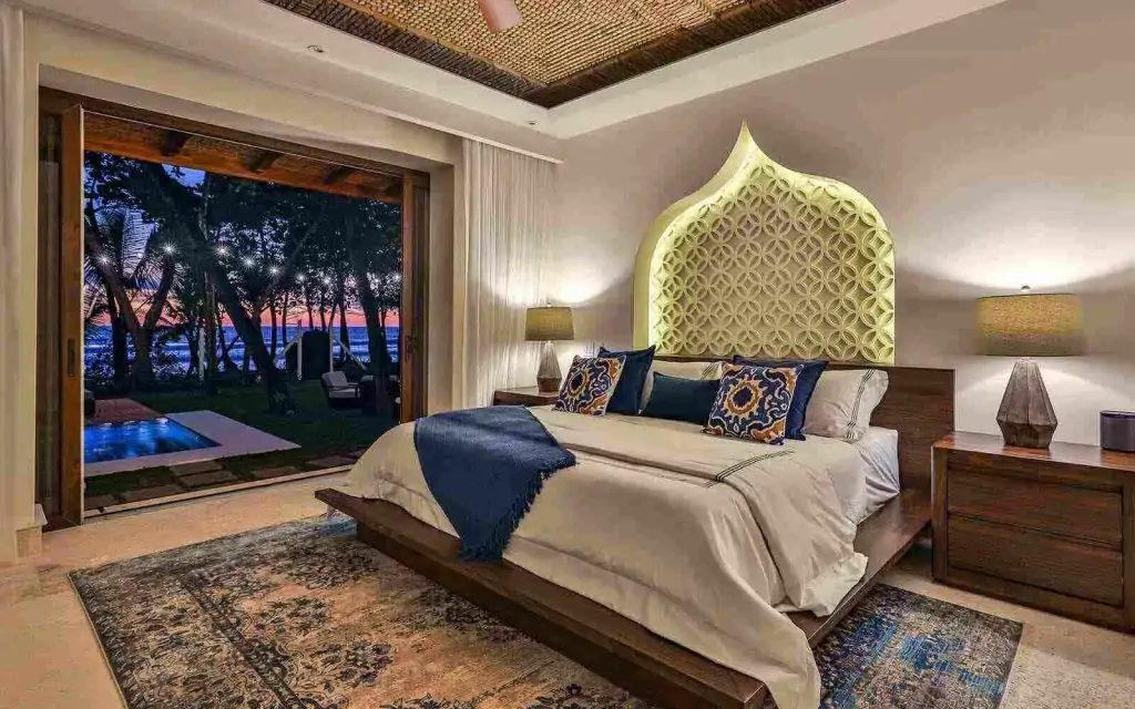 A king-sized bed with a Moroccan architecture wall feature and view to a swimming pool and beachfront at nighttime.