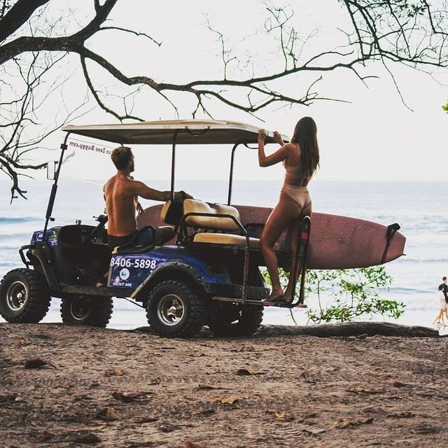 A couple in a cart with surfboards on the beach