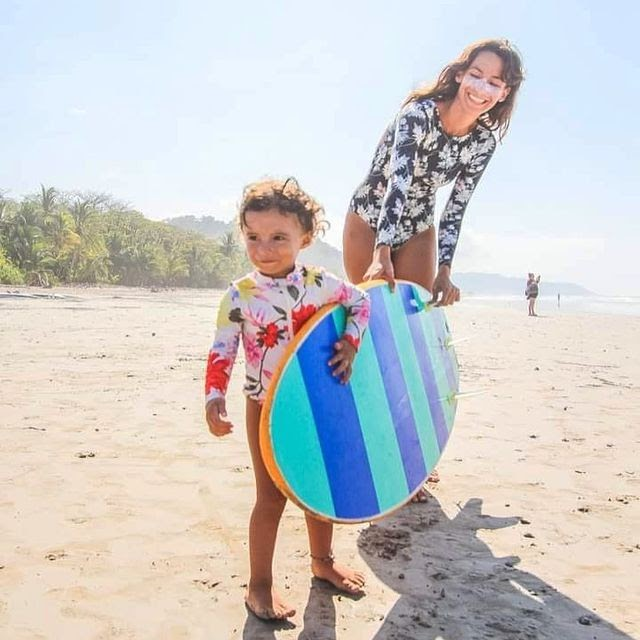 A mother and daughter carrying a surfboard on the beach in the daytime.