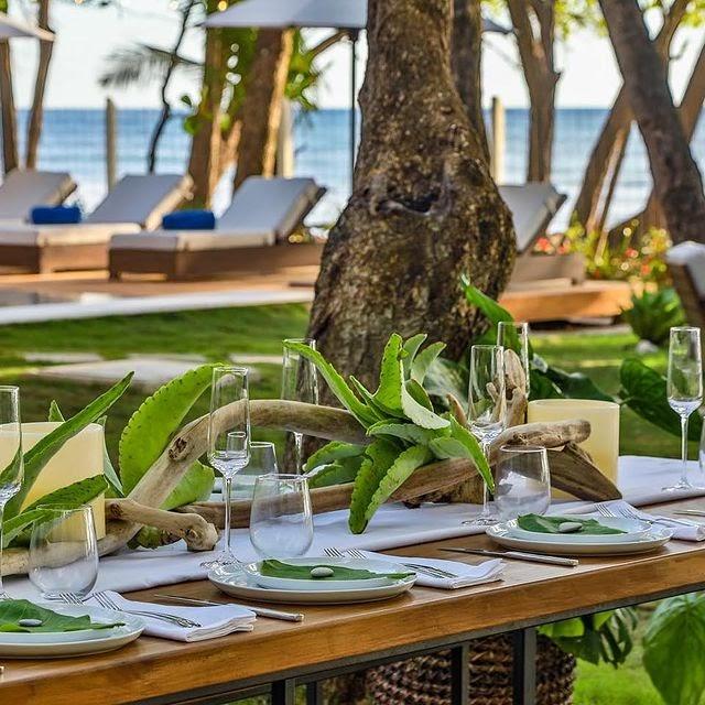 A table set in the lush gardens of Casa Teresa