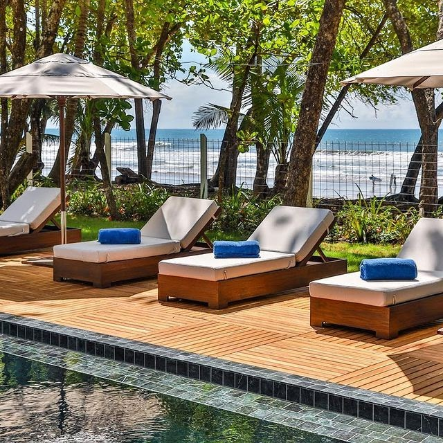 Sunloungers by a swimming pool with an ocean view in the daytime