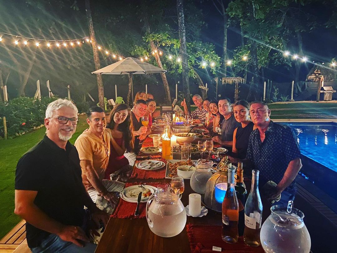 A group of people enjoying beachfront dining at Casa Teresa in the nighttime