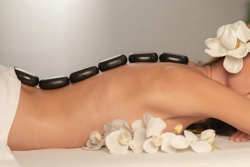 A woman lying on a bed with black rocks placed down her spine.