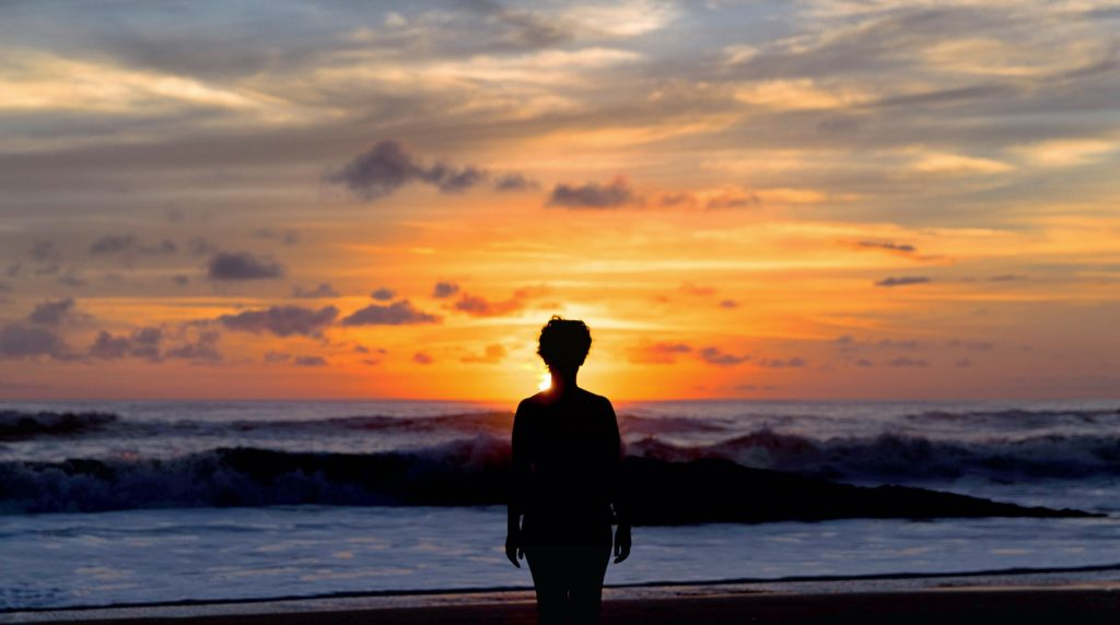 Person standing on the beach in Santa Teresa, Costa Rica at sunset