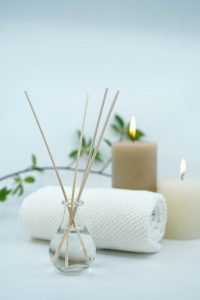 aromatherapy oil fragrance diffuser with rolled blanket and candles in background