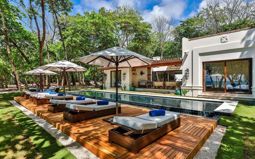A swimming pool and poolside deck chairs at Casa Teresa, Costa Rica